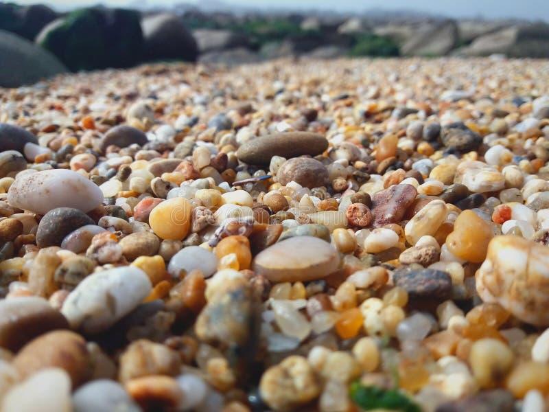 Stenen op een strand in de voorgrond met klippen in backgroun stock fotografie