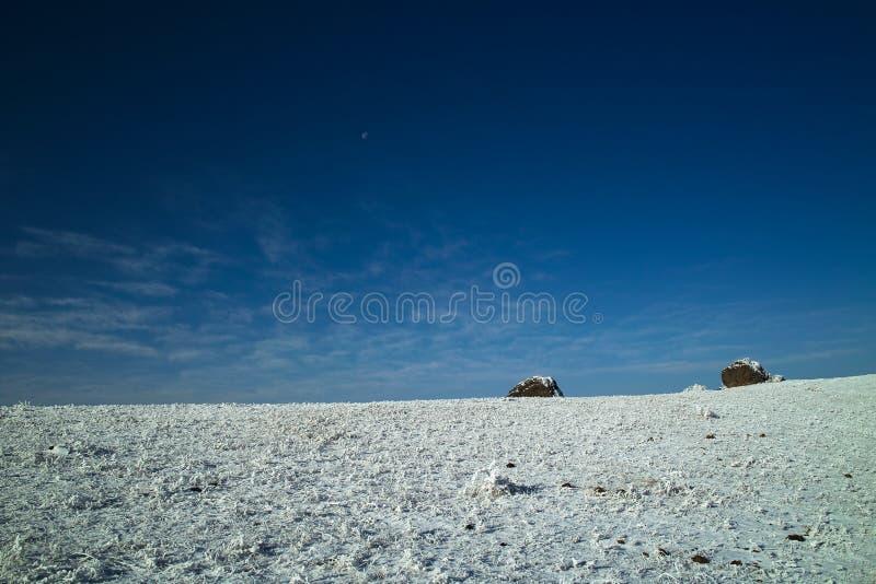 Stenen op snowfield in blauwe hemel stock foto