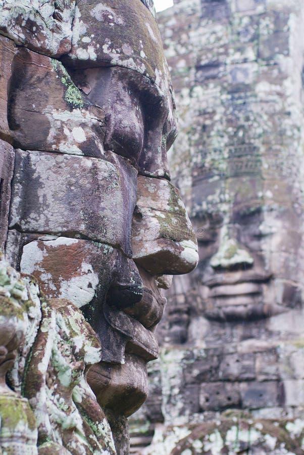Stenen sned framsidor på väggen av den Bayon templet i Siem Reap, Cambodja arkivfoton