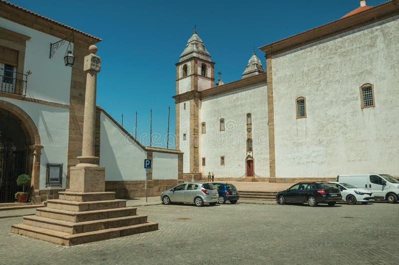 Stenen ställer vid skampålen i en fyrkant med parkerade bilar och den barocka kyrkan royaltyfri bild