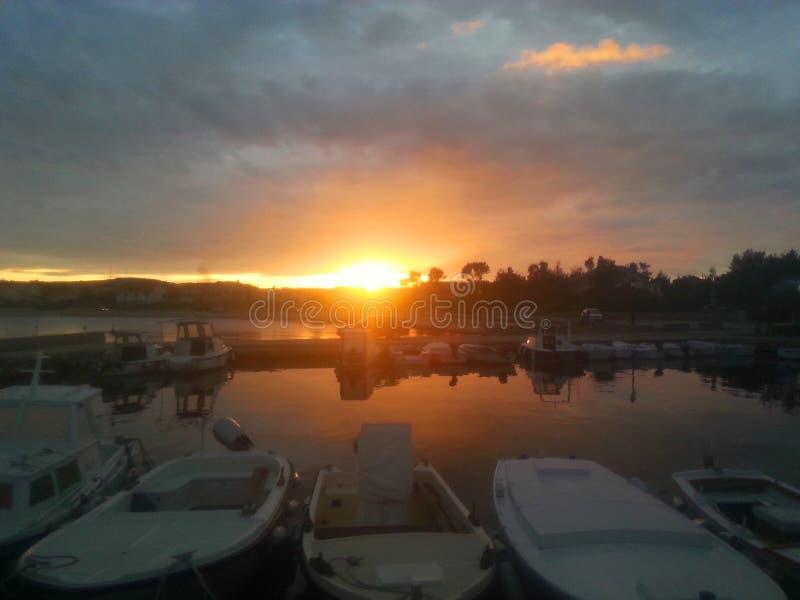 Stenget solnedgång med små fartyg royaltyfri bild