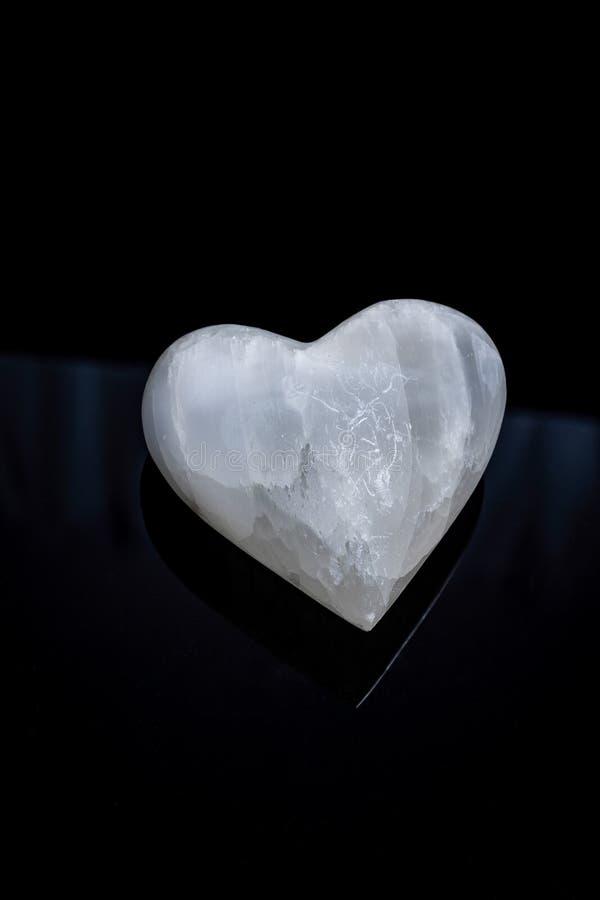 Stenhjärta på svart bakgrund arkivbild