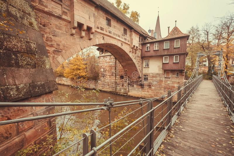 Stenhus och upphängningbro över floden i den historiska staden av Nuremberg med historiska väggar fotografering för bildbyråer