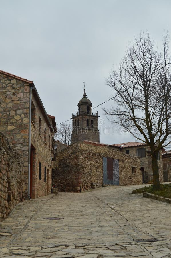 Stenhus på överkanten kan du se det Klocka tornet av domkyrkan i byn av Medinaceli Arkitektur historia, royaltyfria foton