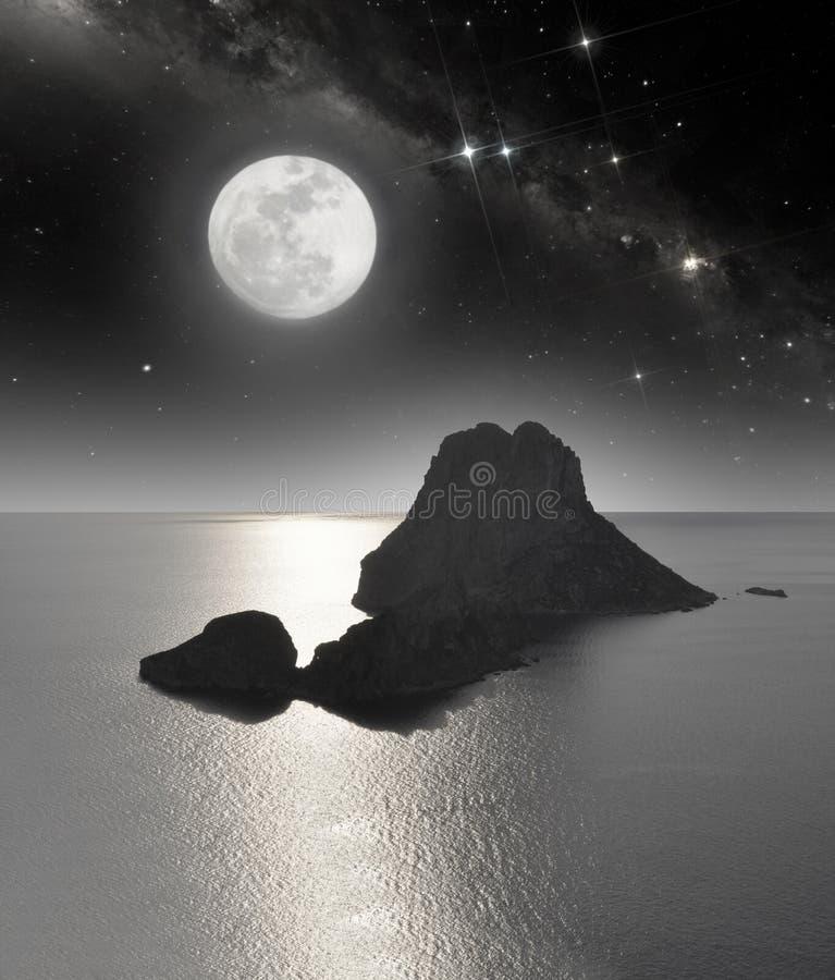 Stenig ö i månsken royaltyfri bild