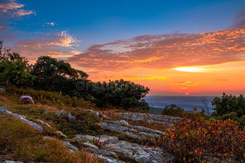 Stenig granit överst av berget på solnedgången royaltyfri foto