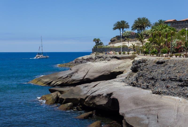 Stenig havkust och fartyg arkivfoton