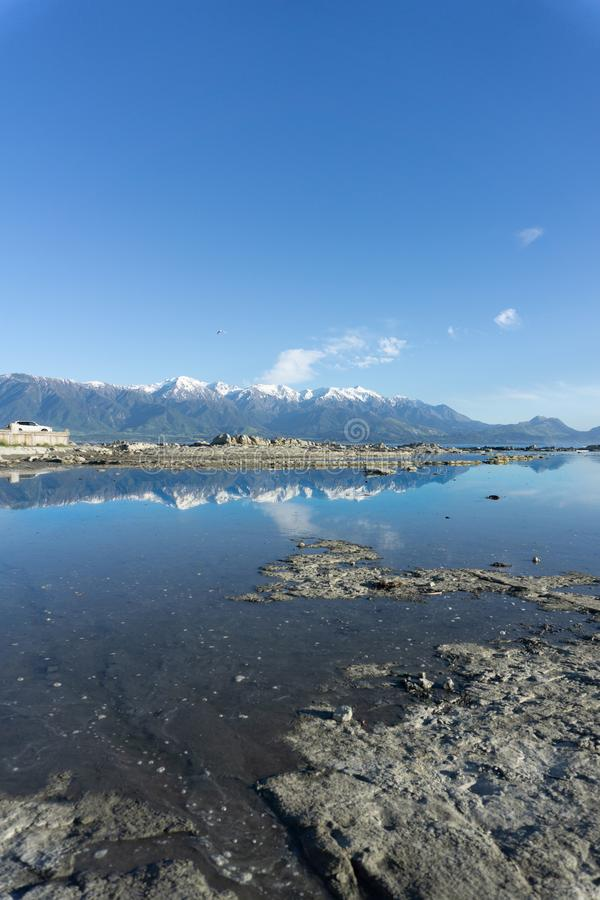 Stenig Kaikoura strand och hav under blå himmel med vita moln royaltyfria bilder