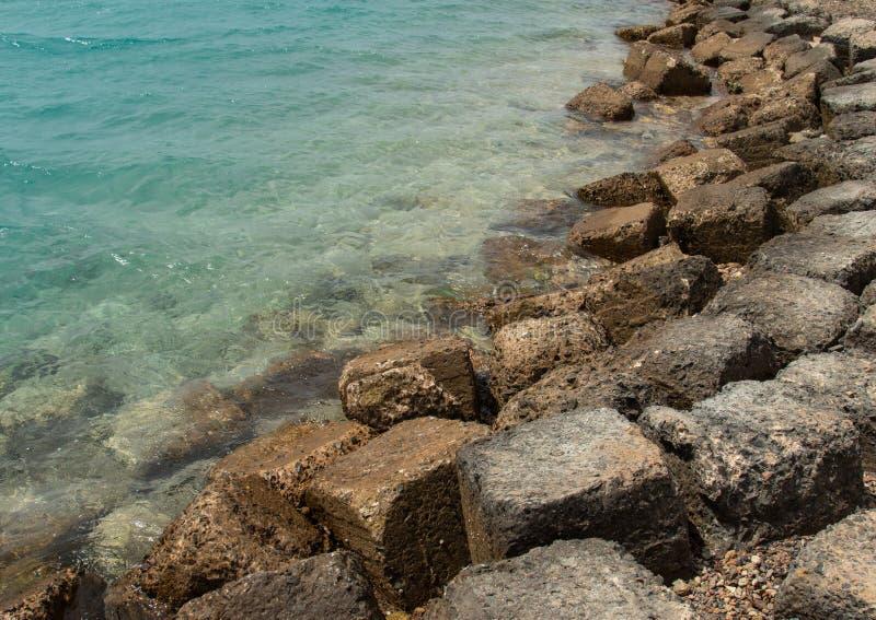 Stenig kust för hav med klart vatten på en öde strand royaltyfri bild