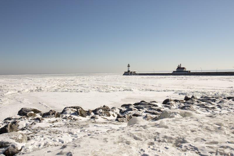 Stenig kust längs djupfrysta Lake Superior med pir och fyrar royaltyfri fotografi