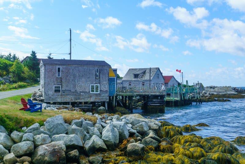 Stenig kust och hus i den indiska hamnen för fiskeläge arkivfoto