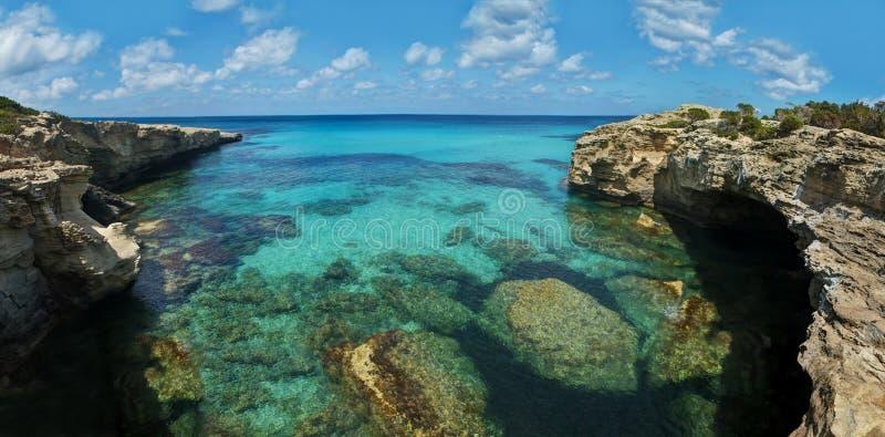 Stenig kust och klart hav med koraller arkivfoton