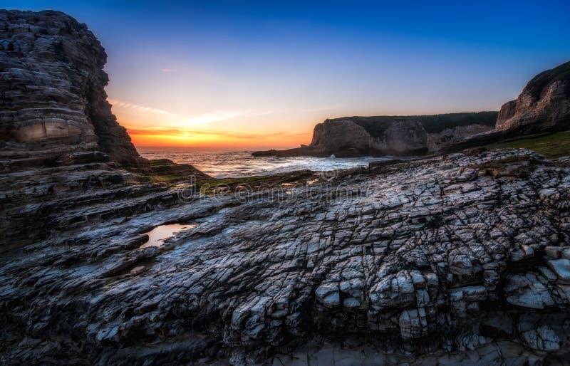 Stenig kust och solnedgång arkivfoton