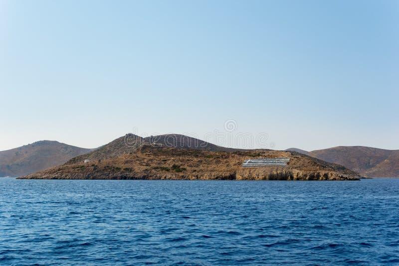 Stenig kustlinje med en stor grekisk flagga i den Kalymnos ön, Dodecanese, Grekland royaltyfri fotografi