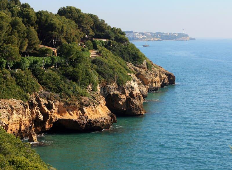 Stenig kustlinje och djungel nära havet med blå himmel arkivfoton