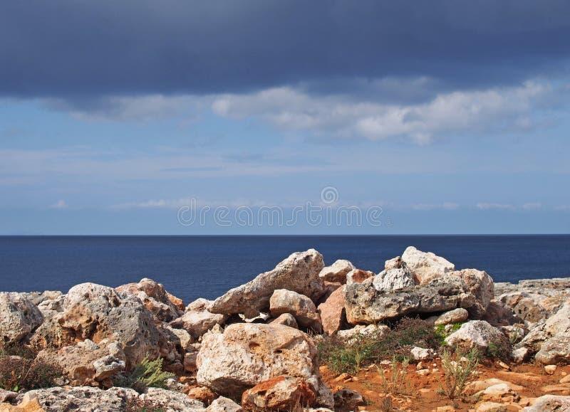 Stenig kustlinjeplats med vita stenar mot ett lugna blå hav och himmel med solljus och moln arkivbild
