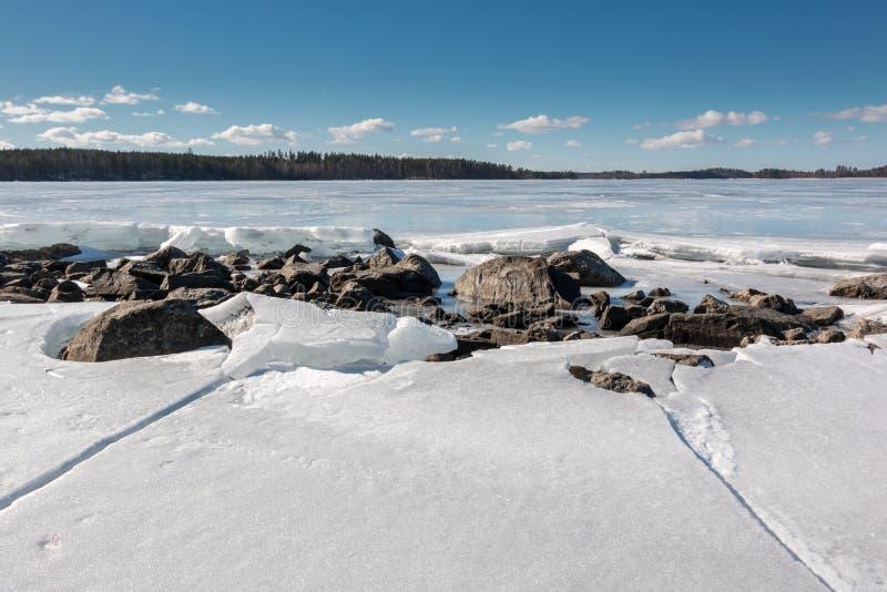 Stenig lakefront med flagig is i vår arkivbilder