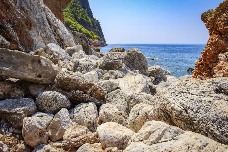 Stenig och stenig kust av det tropiska havet sikt av havet till och med stenar av kustlinjen Berg och hav seascape arkivbilder
