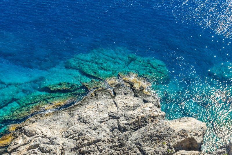 Stenig rev under den Lindos akropolen på den Rhodos ön med det blåa havet royaltyfri foto