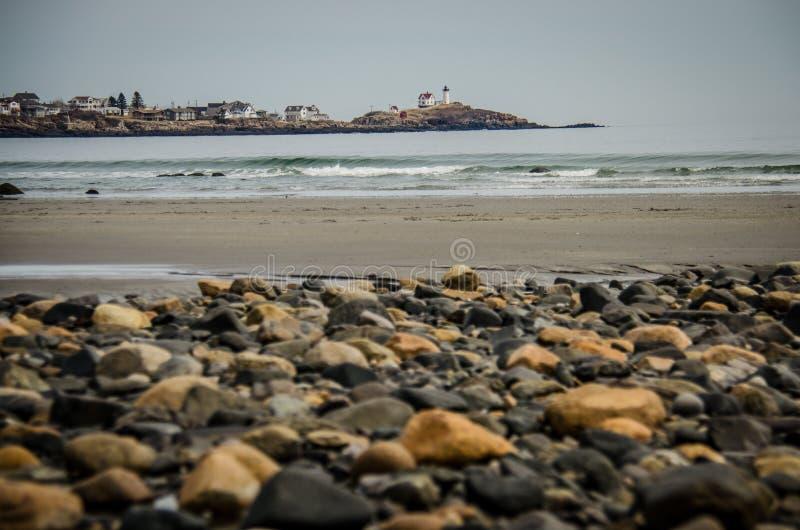 Stenig shorelinekust av Maine med Nubblefyren i bakgrunden royaltyfri fotografi