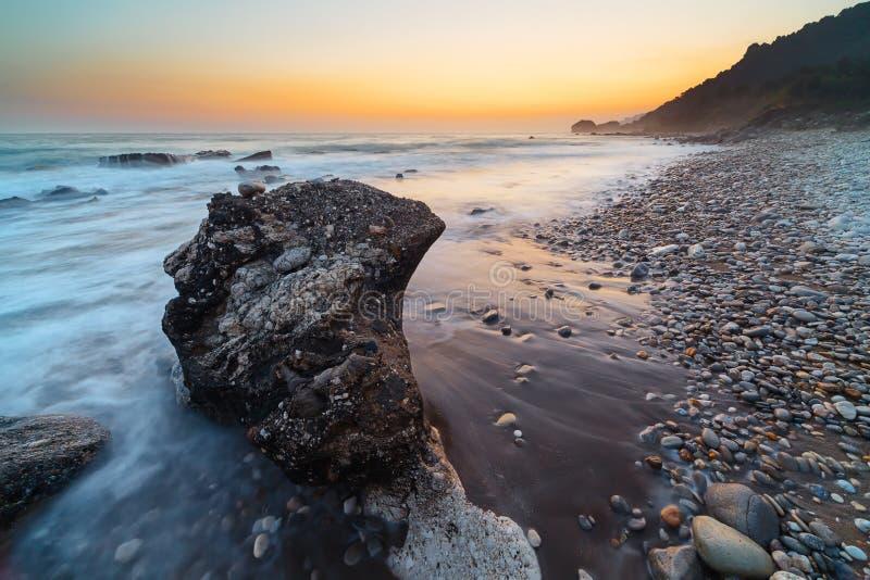 stenig solnedgång för kustlinje arkivfoto