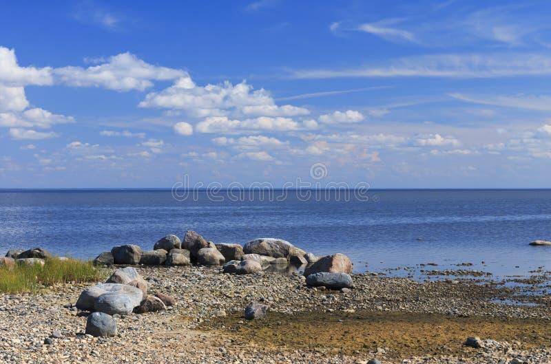 Stenig strand i mitt--sommar arkivfoton