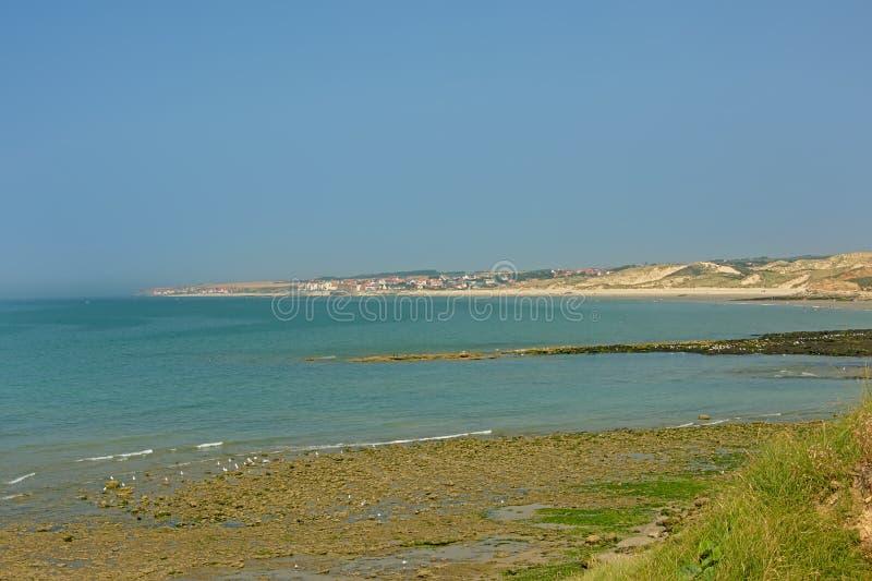 stenig strand med grön havsväxt och en by i bakgrunden längs opalkostnad av Nordsjön i Frankrike royaltyfri fotografi