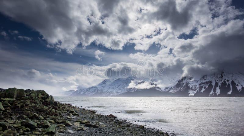 Stenig strand med moln. royaltyfri foto