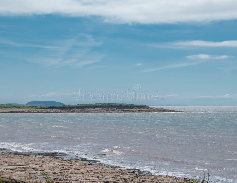Stenig strand och ö arkivfoton