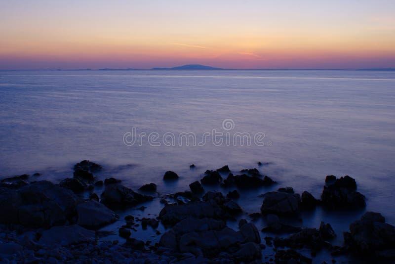 Stenig strand på Pag-ön efter solnedgång royaltyfri bild