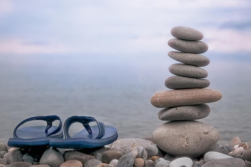 Stenig strand, tung himmel, hav, häftklammermatare och en pyramid av lägenhetgrå färgstenar fotografering för bildbyråer
