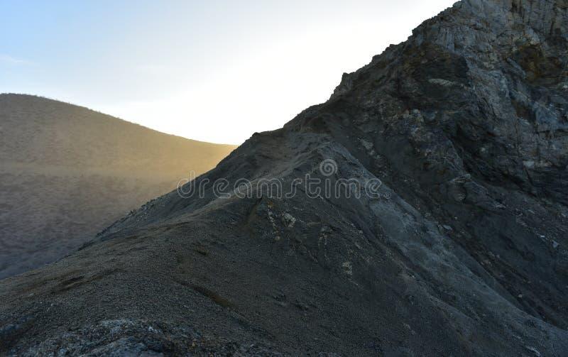 Stenig svart kulle- och sanddyn i Baja, Mexico arkivfoton