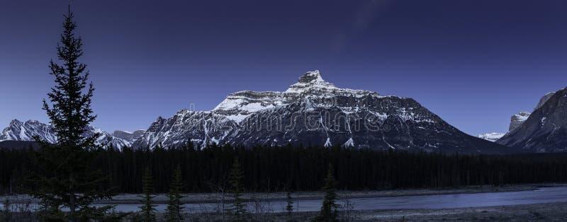 Steniga berg i månskenet längs den härliga blåa floden arkivbild