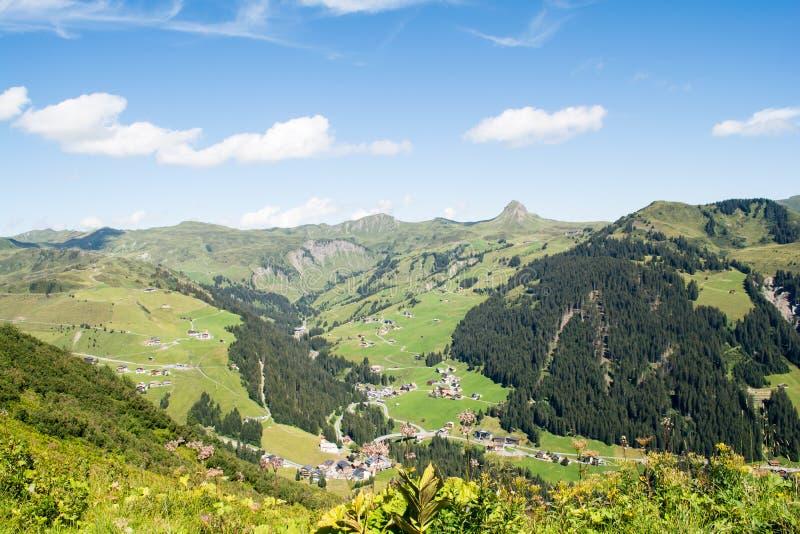 Steniga berg och grönt gräs med solen och den härliga blåa himlen med moln royaltyfria bilder