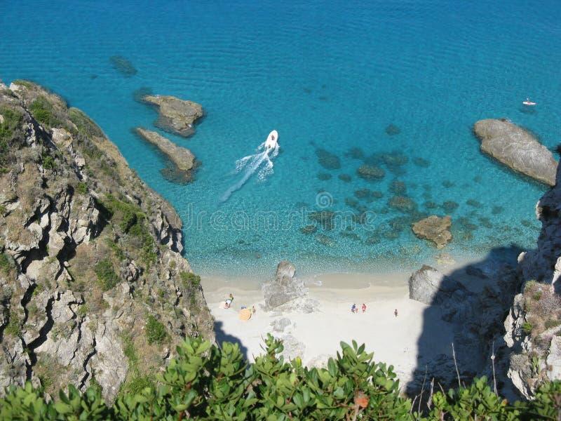 Steniga klippor ovanför havet och stranden arkivfoto