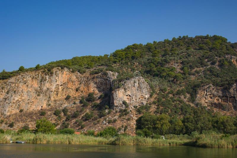 Steniga kuster av floden Dalyan i Turkiet med forntida Lycian gravvalv, selektiv fokus arkivfoton