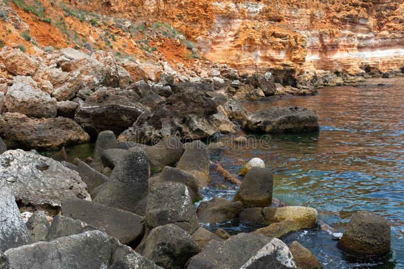 Steniga leraklippor på stranden arkivfoto