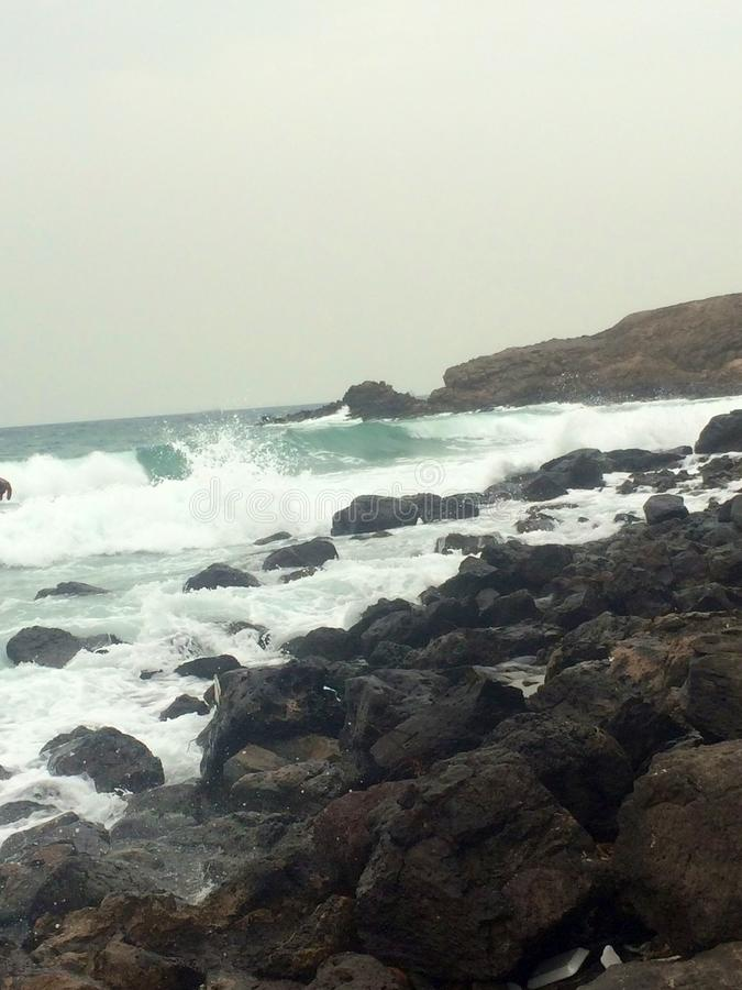 Steniga vågor i havet arkivfoton