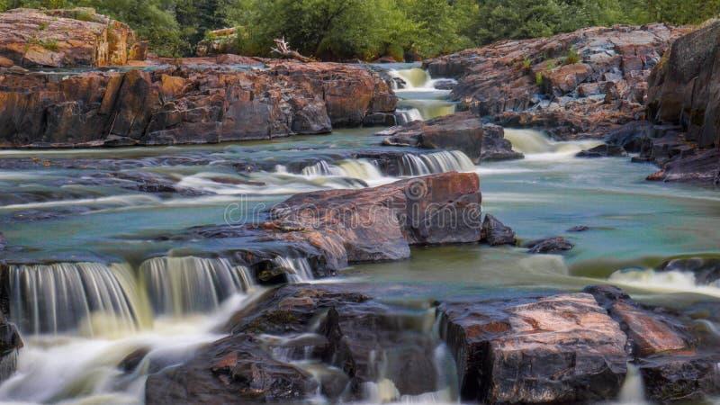 Steniga villebrådet för den färgrika vattenfallet som omges av gröna försök och vaggar det målas fotografering för bildbyråer