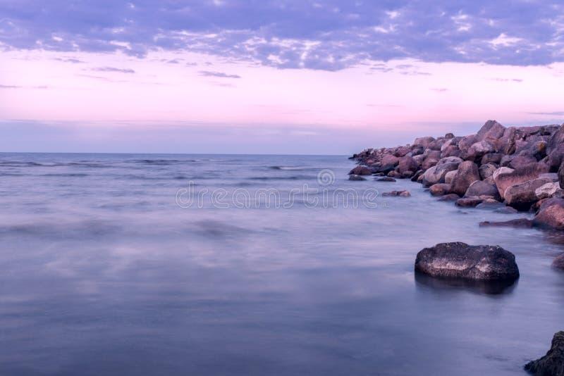 Stenkanten fördjupa in i det baltiska havet i violetta färger royaltyfria bilder