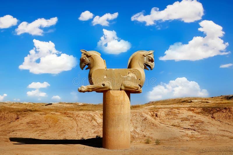 Stenkolonnskulptur av en grip i Persepolis mot en blå himmel med moln Segersymbolet av den forntida Achaemenidsläktingen arkivbild
