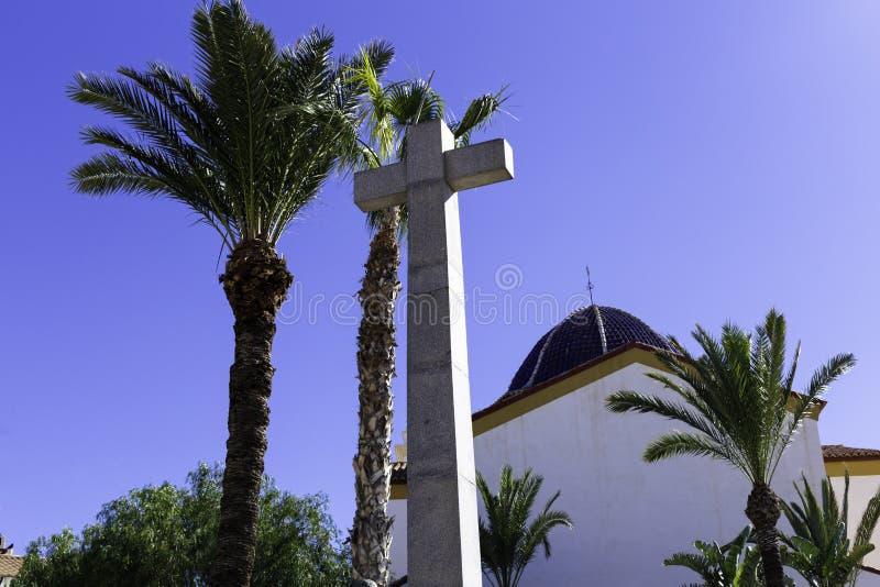 Stenkors och kupolen av kyrkan mot bakgrunden av blå himmel och palmträd Symbol av tro, religion, kristendomen royaltyfri bild