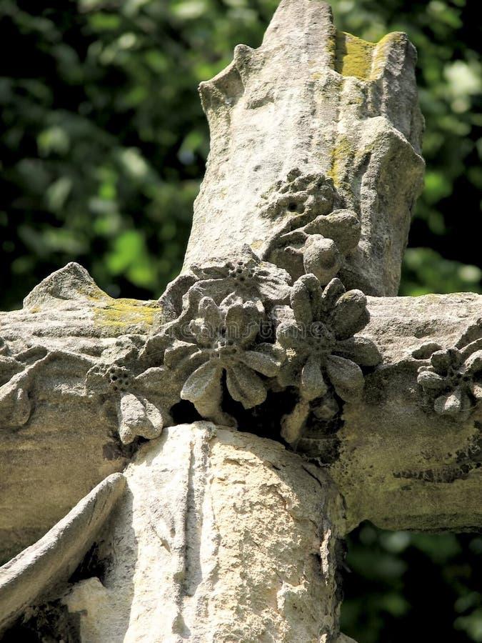 Stenkorsskulptur med blommor arkivfoton