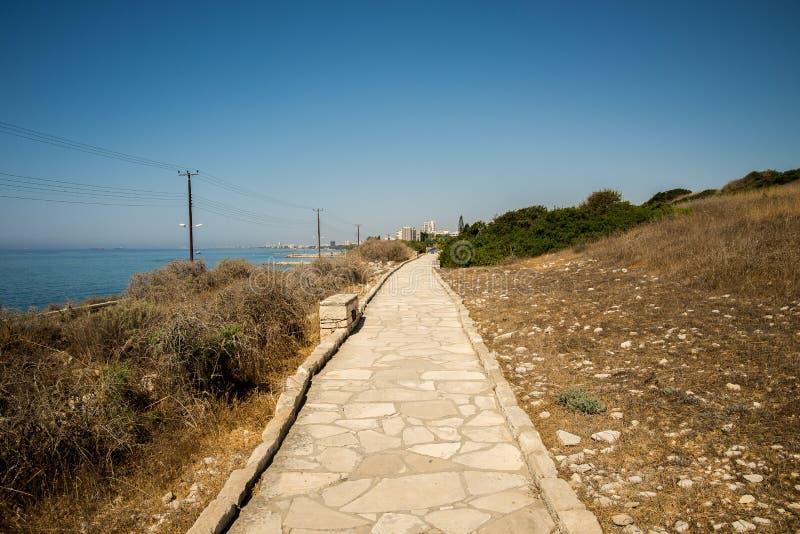 Stenlagd fot- bana längs havet till den forntida akropolplatsen på Limassol royaltyfria bilder