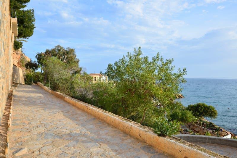 Stenlagd kust- gångbana på en sommarafton arkivfoto