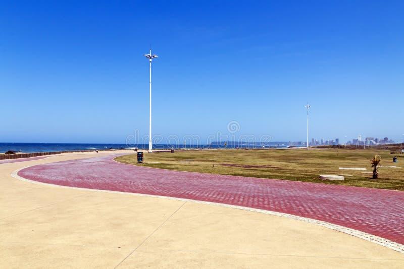 Stenlagd promenadmodell och textur mot havet och himmel arkivfoton