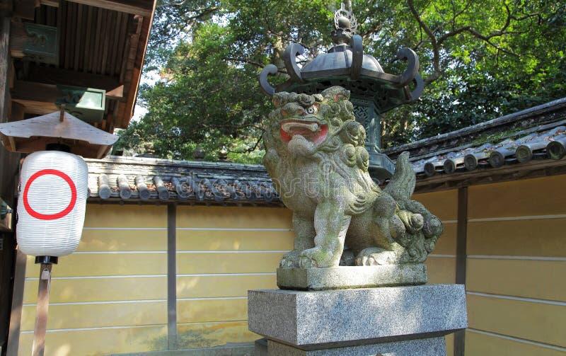 Stenlejonställning bredvid japansk relikskrin arkivbild