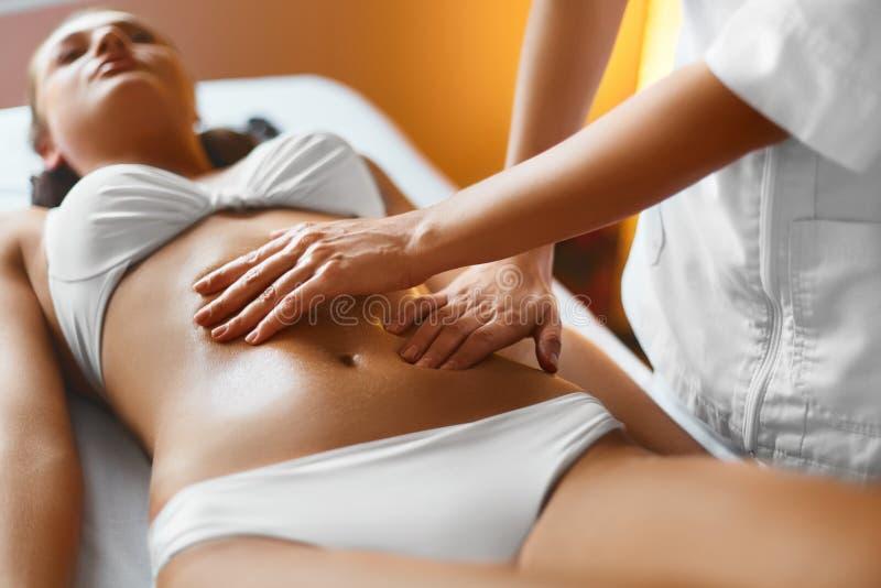 Stenmassage på white kvinna för vatten för brunnsort för hälsa för huvuddelomsorgsfot Massör som gör massage på kvinnakropp i royaltyfri foto