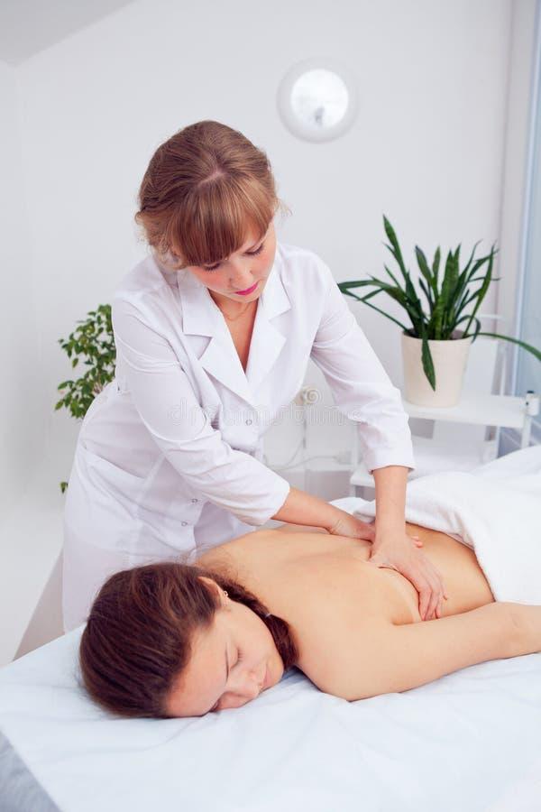 Stenmassage på white Kvinnlig som tycker om koppla av tillbaka massage i den CosmetologySpa mitten Förkroppsliga omsorg, hudomsor arkivbilder