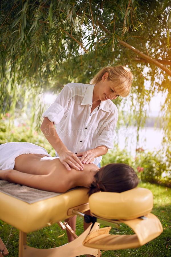 Stenmassage på white Kvinnlig tyckande om massage i natur royaltyfri fotografi